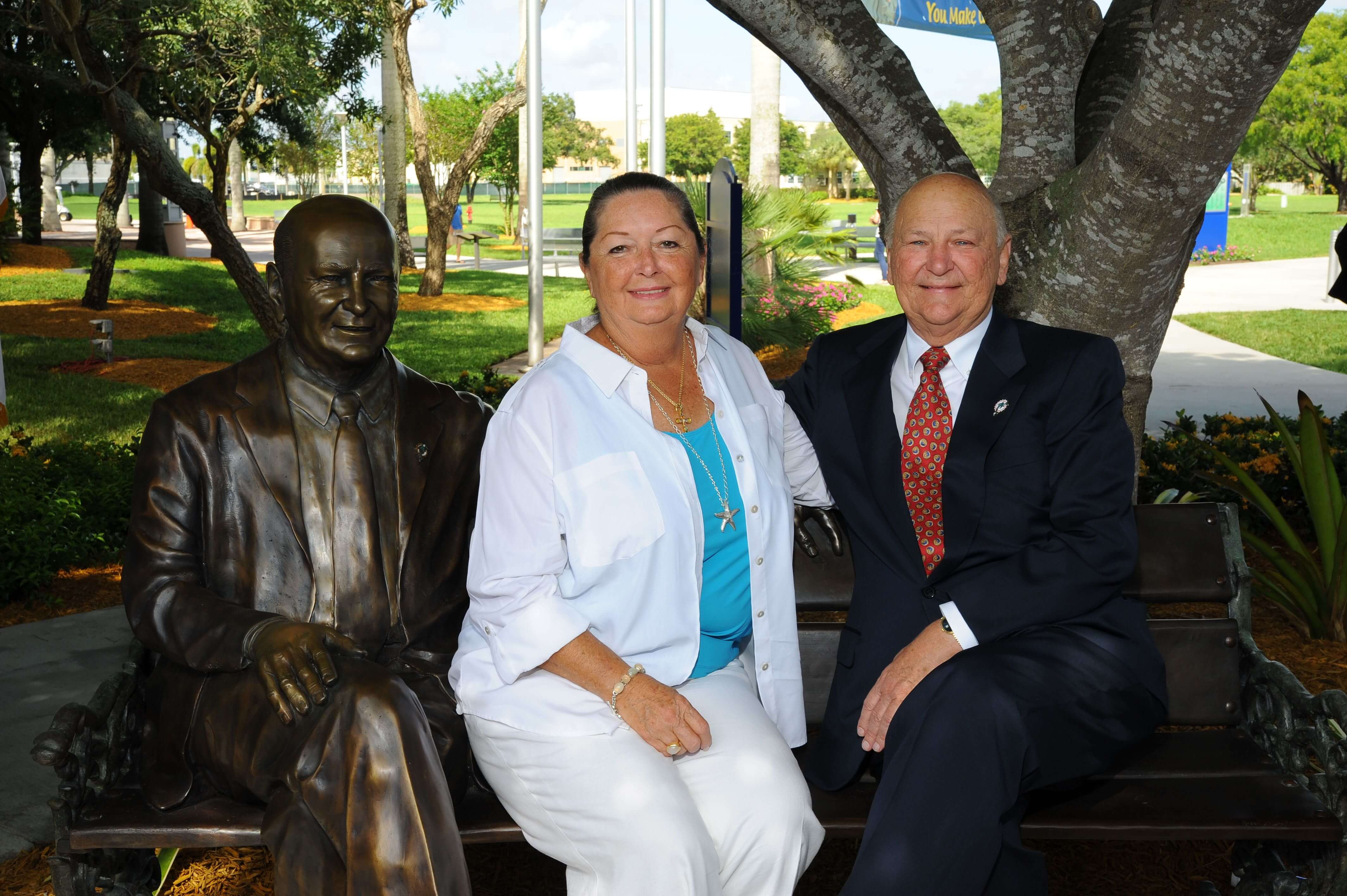 Marti and Wayne Huizenga sit on a bronze bench and statue of Wayne Huizenga on NSU's Davie campus. The sculpture was designed and crafted by nationally acclaimed sculptor Robert St. Croix.