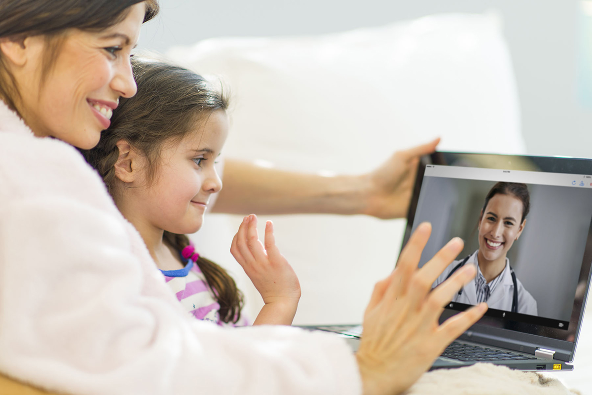 A mother and daughter have a virtual visit with a doctor via an app available from Baptist Health