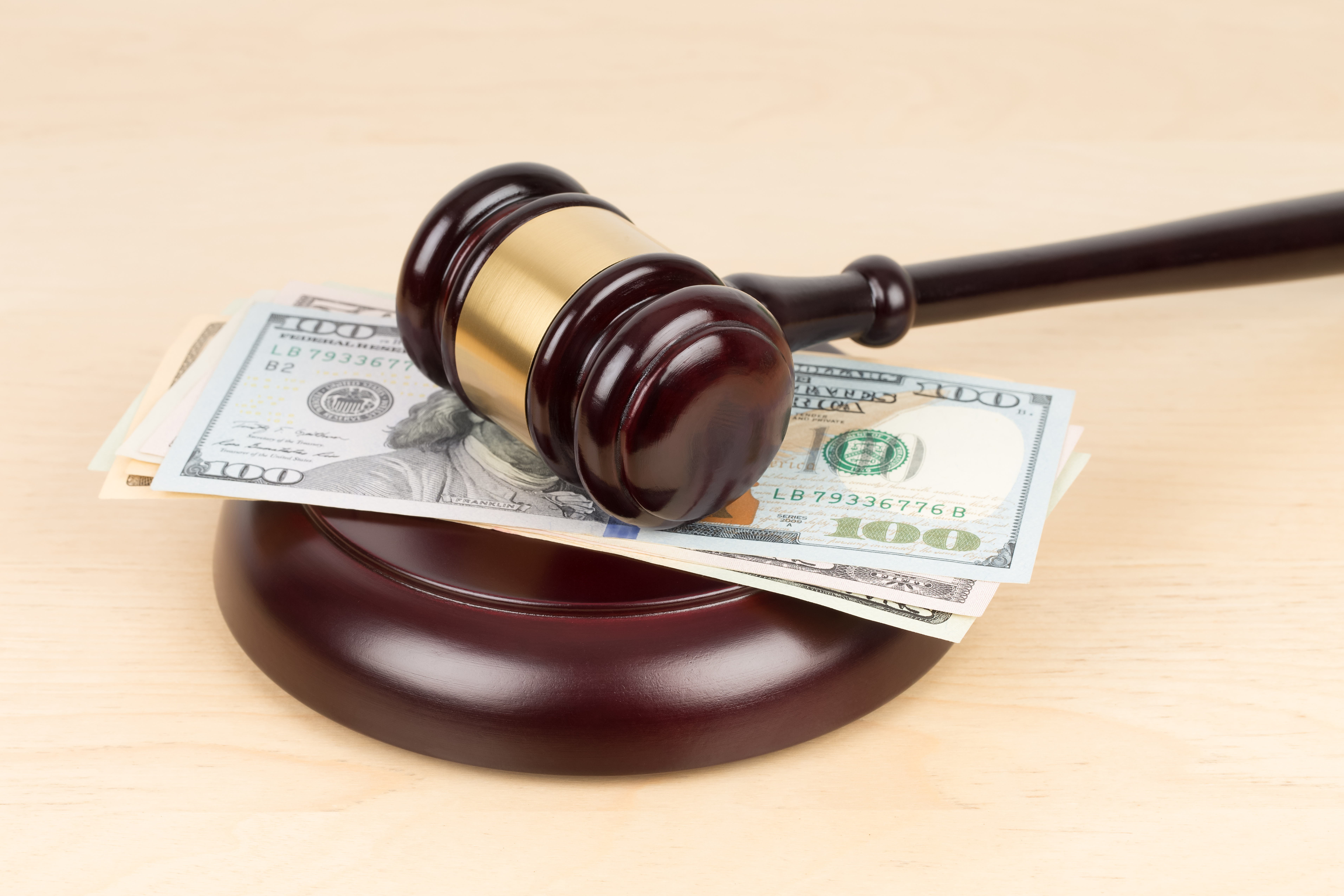 Judge wooden gavel with dollar money banknote