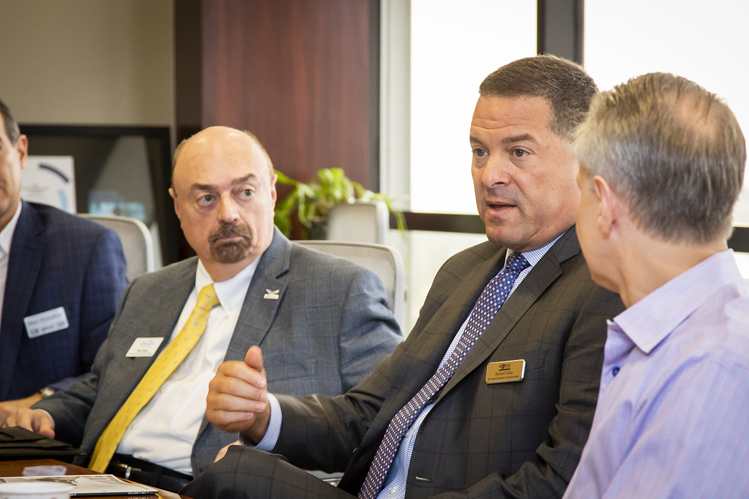 Broward County Commissioner Michael Udine, center, make a point as Ron Drew of the Alliance, left, and Will Fleming listen.