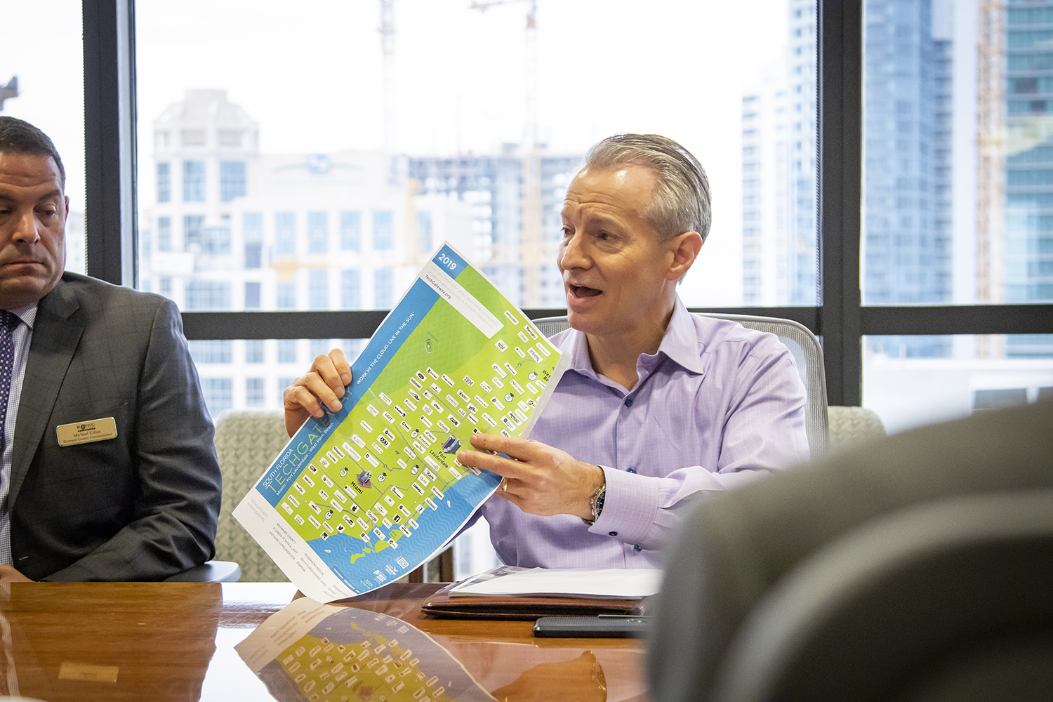 MotionPoint CEO Will Fleming holds a TechGateway map, which provides a visual reference to the abundance of tech firms in South Florida